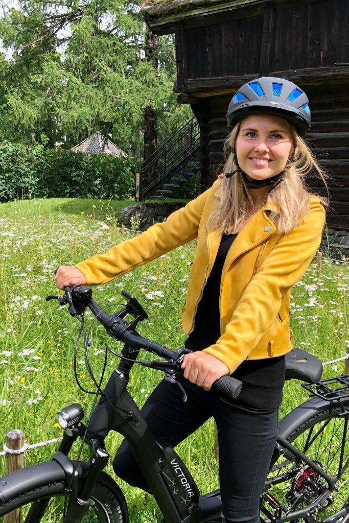 Dame med blå hjelm og gul jakke på elsykkel